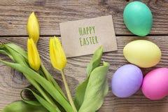 Κάρτα χαιρετισμών Πάσχας, αυγά και τουλίπες στον ξύλινο πίνακα Στοκ εικόνα με δικαίωμα ελεύθερης χρήσης
