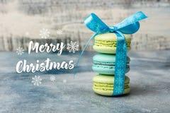 Κάρτα Χαρούμενα Χριστούγεννας τρία macarons δένονται από μια μπλε κορδέλλα στοκ φωτογραφίες