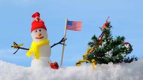 Κάρτα Χαρούμενα Χριστούγεννας, χιονάνθρωπος με το χριστουγεννιάτικο δέντρο στο χειμερινό πάρκο, χαιρετισμός Χριστουγέννων φιλμ μικρού μήκους