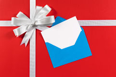 Κάρτα Χριστουγέννων ή γενεθλίων, άσπρο τόξο κορδελλών δώρων, κόκκινο υπόβαθρο, διάστημα αντιγράφων Στοκ Φωτογραφία