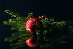 Κάρτα Χριστουγέννων με τα κόκκινα μπιχλιμπίδια και δέντρο γουνών στο μαύρο υπόβαθρο Στοκ Φωτογραφίες