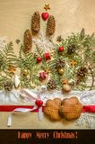 Κάρτα Χριστουγέννων με τα μπισκότα στο κόκκινο τρόχισμα κορδελλών και δαντελλών, καρδιά σοκολάτας με ένα τόξο και κλαδάκια του th Στοκ Εικόνα