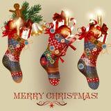 Κάρτα Χριστουγέννων με τις κάλτσες, τα μπιχλιμπίδια, τα κουδούνια και τα δώρα Στοκ Φωτογραφίες