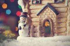 Κάρτα Χριστουγέννων με το σπίτι νεράιδων και το χιονάνθρωπο, μαγική ατμόσφαιρα διακοπών Στοκ Φωτογραφία