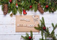 Κάρτα Χριστουγέννων που διακοσμείται με τις κόκκινες σφαίρες, τη γιρλάντα και τους πράσινους κομψούς κλάδους Χριστούγεννα ευτυχή Στοκ εικόνα με δικαίωμα ελεύθερης χρήσης