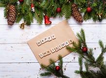 Κάρτα Χριστουγέννων που διακοσμείται με τις κόκκινες σφαίρες, τη γιρλάντα και τους πράσινους κομψούς κλάδους Χριστούγεννα ευτυχή Στοκ φωτογραφία με δικαίωμα ελεύθερης χρήσης