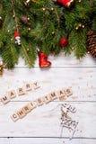 Κάρτα Χριστουγέννων που διακοσμείται με τις κόκκινες σφαίρες, τη γιρλάντα και τους πράσινους κομψούς κλάδους Χριστούγεννα ευτυχή Στοκ Εικόνες