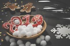 Κάρτα Χριστουγέννων: σε ένα ξύλινο πιάτο είναι κόκκινα μπισκότα πιπεροριζών με μορφή των αριθμών το 2019 και άσπρα στρογγυλά snow στοκ εικόνα με δικαίωμα ελεύθερης χρήσης