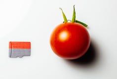 Κάρτα MicroSD δίπλα στην ντομάτα κερασιών Στοκ Εικόνες
