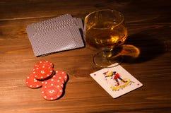 Κάρτες παιχνιδιού και ποτήρι κρασιού του κονιάκ στον ξύλινο πίνακα Στοκ Εικόνες