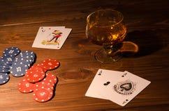 Κάρτες παιχνιδιού και ποτήρι κρασιού του κονιάκ στον ξύλινο πίνακα Στοκ εικόνες με δικαίωμα ελεύθερης χρήσης