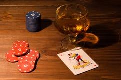 Κάρτες παιχνιδιού και ποτήρι κρασιού του κονιάκ στον ξύλινο πίνακα Στοκ φωτογραφίες με δικαίωμα ελεύθερης χρήσης