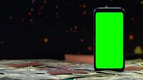 Κάρτες παιχνιδιού που αφορούν το γραφείο με τα μετρητά και το πράσινο smartphone οθόνης, νίκες φιλμ μικρού μήκους
