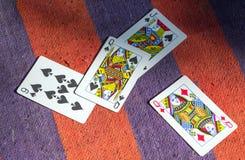 Κάρτες παιχνιδιού σε ένα ριγωτό χαλί στοκ εικόνες