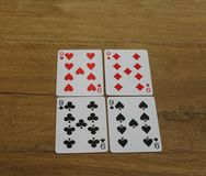 Κάρτες πόκερ σε ένα ξύλινο backround, σύνολο nines των λεσχών, των διαμαντιών, των φτυαριών, και των καρδιών Στοκ Εικόνα