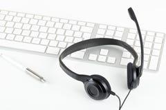 Κάσκα υπολογιστών με το μικρόφωνο στο πληκτρολόγιο υπολογιστών στο άσπρο τ Στοκ Εικόνες