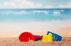 Κάστρα και φτυάρι παιχνιδιών παιδιών στην άμμο ενάντια στη θάλασσα Στοκ Εικόνες
