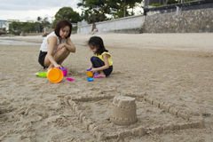 Κάστρο άμμου οικοδόμησης μητέρων και κορών Στοκ Εικόνες