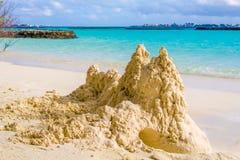 Κάστρο άμμου στην παραλία μπροστά από τον ωκεανό με το αρσενικό στην πλάτη Στοκ φωτογραφία με δικαίωμα ελεύθερης χρήσης