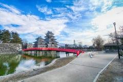 Κάστρο του Ματσουμότο ενάντια με την κόκκινη ξύλινη γέφυρα πέρα από το κανάλι ι Στοκ εικόνες με δικαίωμα ελεύθερης χρήσης
