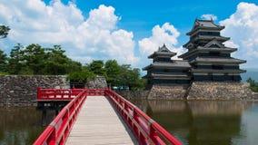 Κάστρο του Ματσουμότο και κόκκινη γέφυρα, Ιαπωνία Στοκ Φωτογραφία