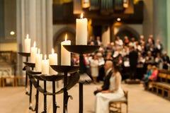 Κάτοχος κεριών με τα κεριά και θολωμένοι άνθρωποι στην εκκλησία στοκ εικόνα