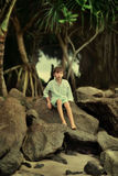 Κάτω από ένα δέντρο σε έναν μεγάλο βράχο κάθεται ένα αγόρι Στοκ Εικόνα