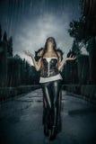 Κάτω από τη θύελλα, όμορφη γυναίκα βαμπίρ στην πύλη παλατιών, γοτθική στοκ φωτογραφίες