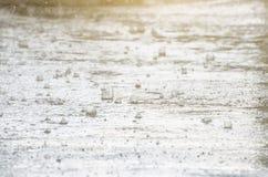 κάτω από τη λασπώδη οδό σταγόνων βροχής βροχής λακκούβας δερμάτων πρώτου πλάνου εκεί σε ορατό οι σταγόνες βροχής είναι ορατές στο Στοκ φωτογραφία με δικαίωμα ελεύθερης χρήσης