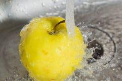 Κάτω από το ρεύμα του νερού η κίτρινη Apple στο νεροχύτη Στοκ Εικόνες