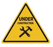 Κάτω από το τριγωνικό προειδοποιητικό σημάδι κατασκευής στο άσπρο υπόβαθρο Στοκ Εικόνα