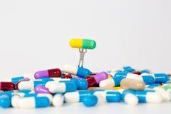 Κάψα φαρμάκων με τους μικροσκοπικούς ανθρώπους Στοκ Εικόνες