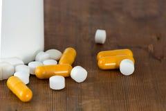 Κάψες και άσπρα στρογγυλά χάπια από ένα μπουκάλι ιατρικής Στοκ Φωτογραφίες