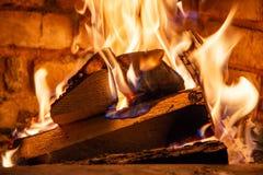 Κάψιμο καυσόξυλου στα εγκαύματα πυρκαγιάς στην εστία Ο φούρνος τούβλου δίνει τη θερμότητα και τη θερμότητα από τα μμένα κούτσουρα στοκ φωτογραφίες