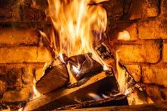 Κάψιμο καυσόξυλου στα εγκαύματα πυρκαγιάς στην εστία Ο φούρνος τούβλου δίνει τη θερμότητα και τη θερμότητα από τα μμένα κούτσουρα στοκ φωτογραφία