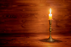 Κάψιμο του παλαιού κεριού με το εκλεκτής ποιότητας κηροπήγιο ορείχαλκου στην ξύλινη πλάτη Στοκ εικόνα με δικαίωμα ελεύθερης χρήσης
