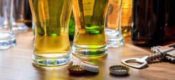 Κάψουλες μπύρας και ποτήρια της μπύρας σε ένα υπόβαθρο μπαρ Στοκ φωτογραφία με δικαίωμα ελεύθερης χρήσης