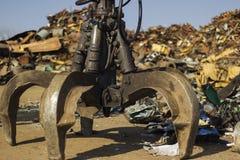 Κάδος αρπαγών κάκτων στο junkyard με το θολωμένο υπόβαθρο σωρών στοκ εικόνες