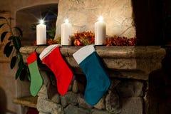 Κάλτσες γυναικείων καλτσών Χριστουγέννων στο υπόβαθρο εστιών στοκ εικόνες