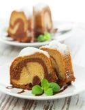 Κέικ βανίλιας και σοκολάτας που τεμαχίζεται με τη μέντα laves στην ξύλινη ετικέττα στοκ φωτογραφία