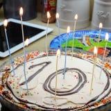 κέικ 10 γενεθλίων με ένδεκα κεριά με την κρέμα και τις καραμέλες Στοκ Εικόνες
