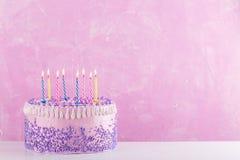 Κέικ γενεθλίων με τα ζωηρόχρωμα κεριά πέρα από το ρόδινο υπόβαθρο Στοκ φωτογραφία με δικαίωμα ελεύθερης χρήσης
