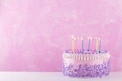 Κέικ γενεθλίων με τα ζωηρόχρωμα κεριά πέρα από το ρόδινο υπόβαθρο Στοκ Εικόνες