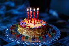 Κέικ γενεθλίων για τα παιδιά με τις ζωηρόχρωμες πτώσεις και τα κεριά Στοκ Εικόνες