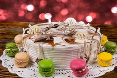Κέικ για το νέο έτος με τα macarons στο ξύλινο γραφείο, φωτεινό ρόδινο ligh Στοκ Εικόνα