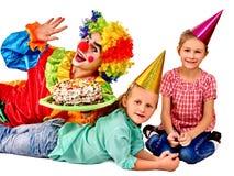 Κέικ εκμετάλλευσης κλόουν στα γενέθλια με τα παιδιά ομάδας Στοκ εικόνα με δικαίωμα ελεύθερης χρήσης