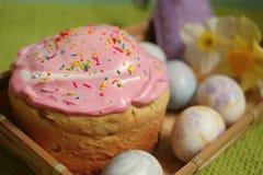 Κέικ και αυγά Πάσχας με τα daffodils σε μια ξύλινη πιατέλα Στοκ Εικόνα