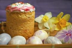 Κέικ και αυγά Πάσχας με το μπλε υπόβαθρο daffodilson Στοκ Εικόνες