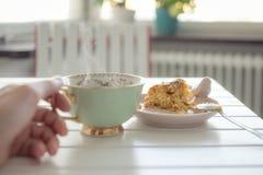 Κέικ και το χέρι που κρατά ένα φλυτζάνι του τσαγιού Στοκ Εικόνα