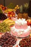 Κέικ και φρούτα στον πίνακα διακοπών Στοκ Εικόνες